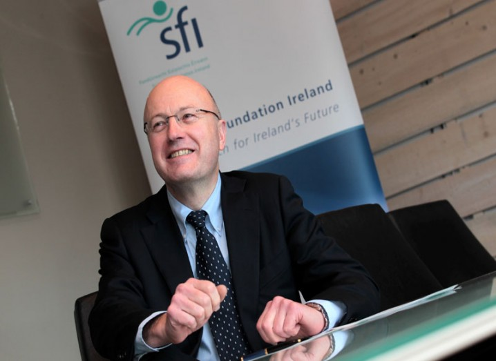 Prof Mark Ferguson of SFI is speaking to someone off-camera while sitting at a desk in front of a branded pop-up banner.