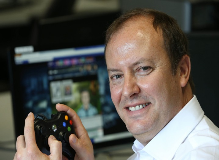 Andrew Day smiling holding a game console controller.