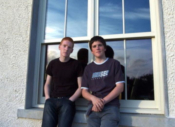 Two boys sitting on a window sill.