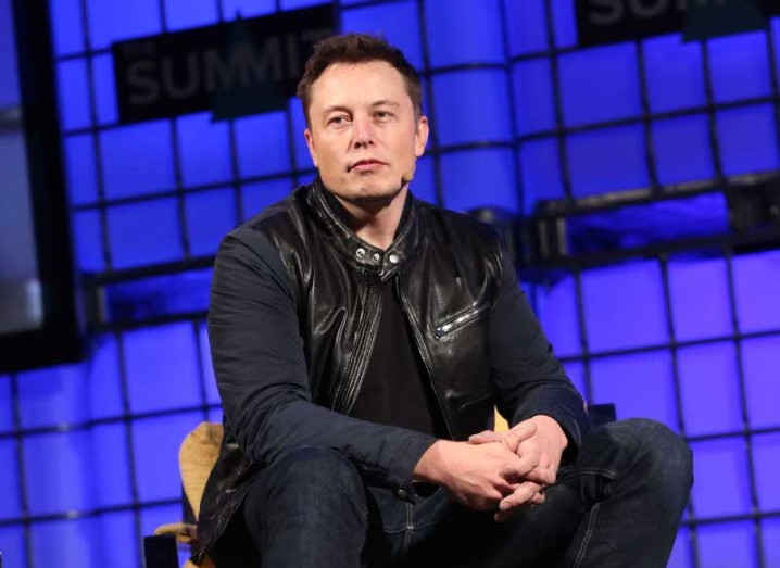 Elon Musk is dressed all in black, sitting on a stage with blue lights behind him.