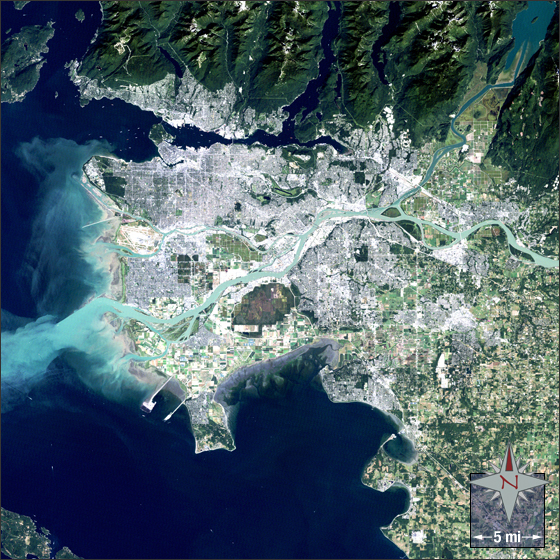A Landsat 5 image of Vancouver in Canada. The image was taken in August 2011. In this image Vancouver appears grey and white. Vegetation is green, water is blue and bare ground is tan. Credit: NASA