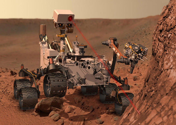 Artist's concept depicting the Curiosity rover using its ChemCam instrument to investigate the composition of a rock surface. ChemCam fires invisible laser pulses at a target, which is simulated with a grey line. The instrument then views the resulting spark with a telescope and spectrometers to identify the chemical elements. Image via NASA/JPL