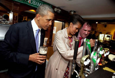 US President Barack Obama and First Lady Michelle Obama take a sip of Guiness in Monegall, Ireland on 23 May 2011