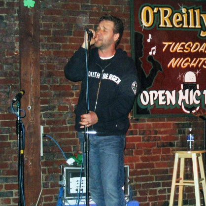 Russell Crowe captured singing on an open mic night at O'Reilly's pub in St. John's, Canada. 13 June 2005. Image credit: Alan Doyle, via Wikimedia Commons