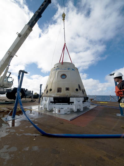 The SpaceX crew pictured bringing Dragon back to the barge where aDragon depicted in orbit, with its retractable solar panels. Image courtesy of SpaceX  crane lifted it from the water after Dragon went into orbit last year. Credit: SpaceX/Mike Altenhofen
