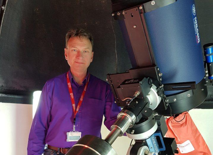 man with greying hair wearing purple shirt and red lanyard standing beside a telescope.