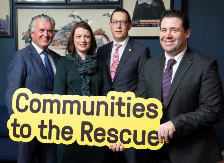 One woman and three men hold a sign that says 'Communities to the Rescue'.