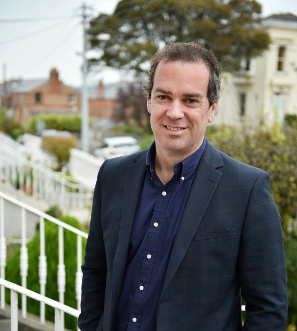 gavin carpenter outside on steps with houses and greenery in background