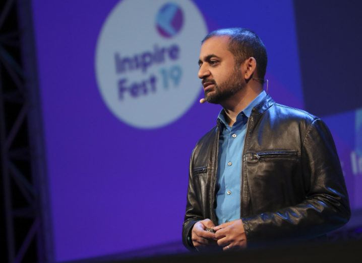 A sallow man with a shaved head in a leather jacket looks at the audience he is addressing against a multicoloured background.