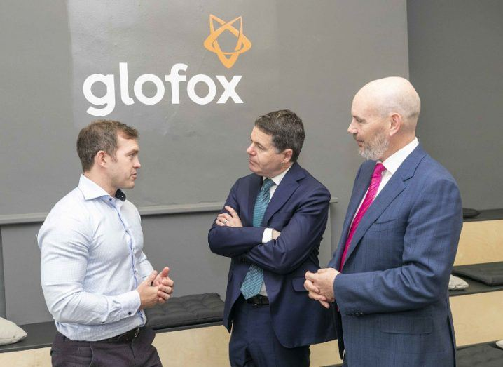 Three men in business attire standing and talking in front of Glofox logo at Silicon Valley Bank funding launch.