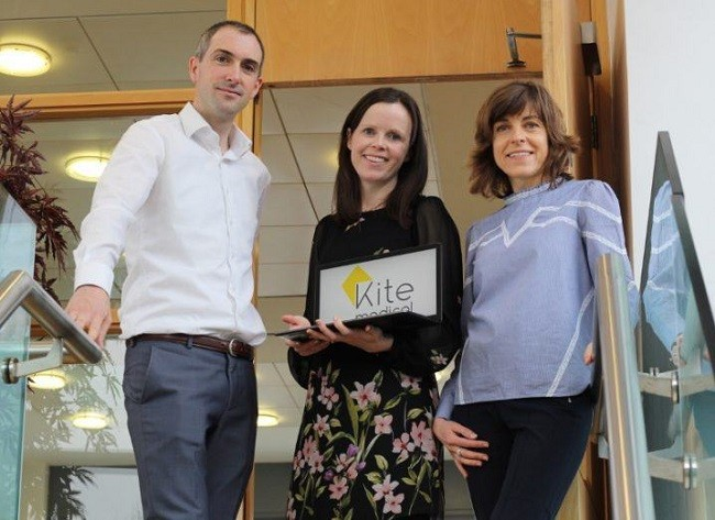 Paul Frehill, Sarah Loughney and Joan Fitzpatrick of Kite Medical standing at the top of stairs smiling and holding a branded laptop.