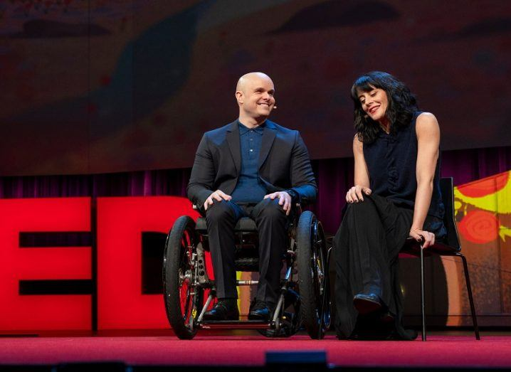 Mark Pollock and Simone George smiling while addressing the TED audience in 2018.