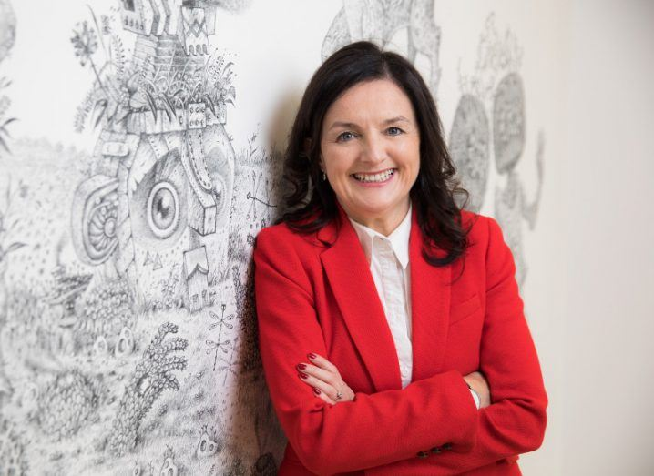 woman with black hair wearing bright red blazer and white shirt smiling broadly with arms folded against a white wall with grey pattern.