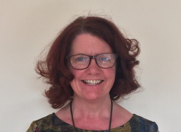 middle-aged woman with short red curly hair and glasses smiling broadly at the camera.