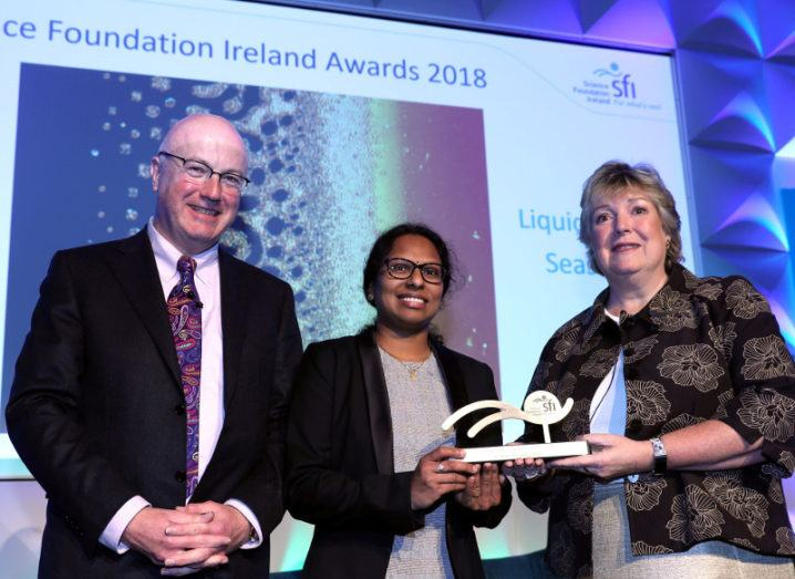 bald man with glasses on stage beside two women holding award against purple backdrop for SFI.