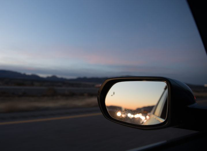 left side view car mirror reflecting lights of cars behind it on a road at dusk, with pink sky overhead.