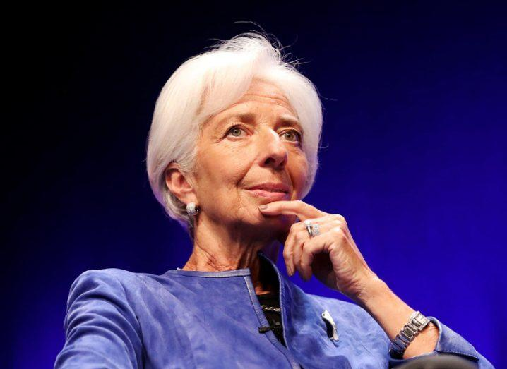 christine lagarde wearing royal blue jacket with finger under chin in pensive pose