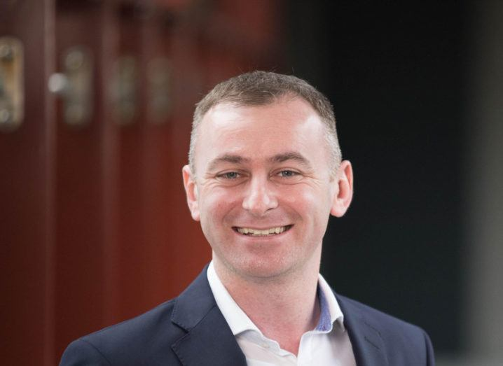 man in his thirties wearing white shirt and black suit jacket smiling broadly at camera.