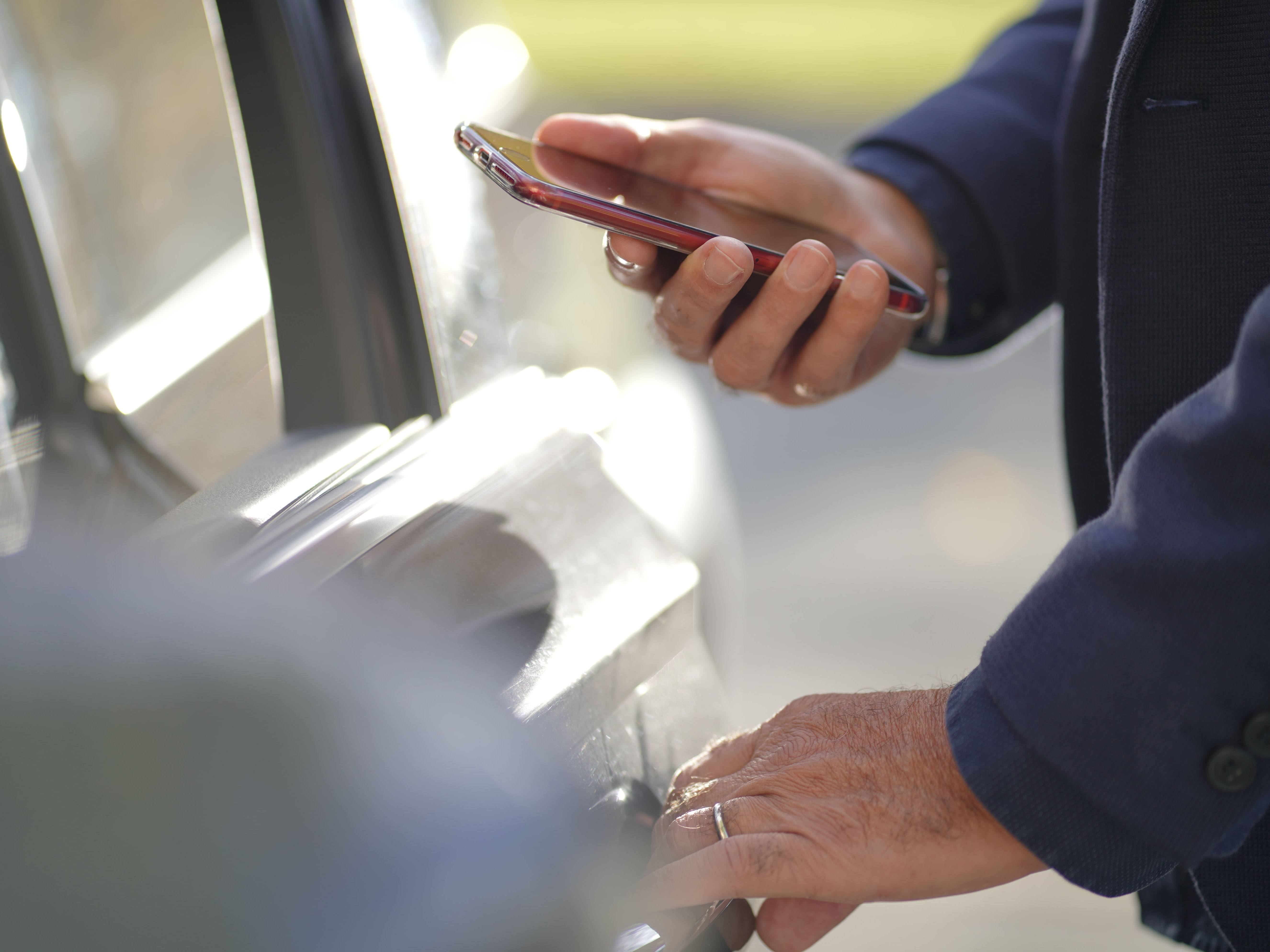 Closeup of a man in blue jacket unlocking door system of his car with a smartphone.