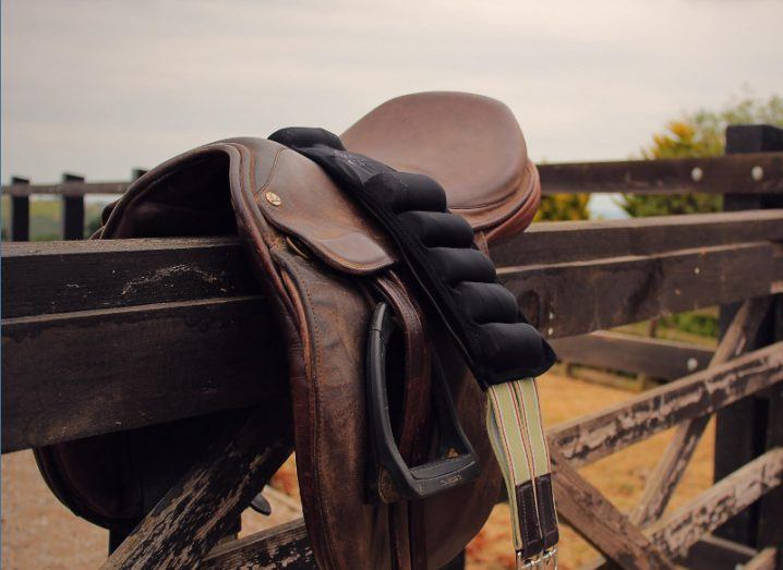 saddle girth draped over a dark wooden fence in a rural setting.