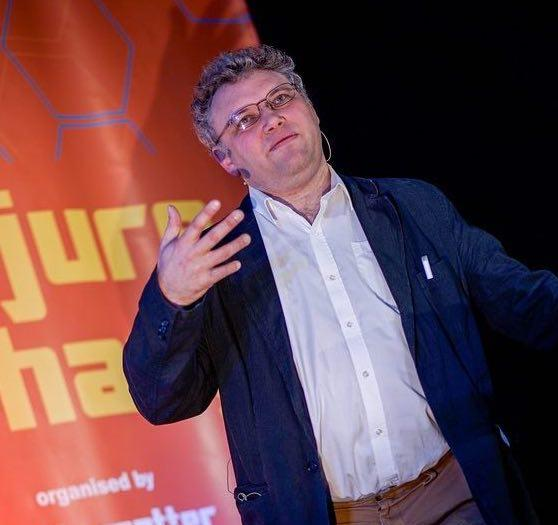 man with curly grey hair and glasses gesturing with hand speaking on stage.