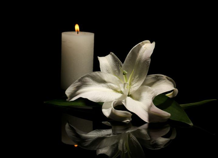 White lily beside burning candle on dark background, symbolising a deceased person.