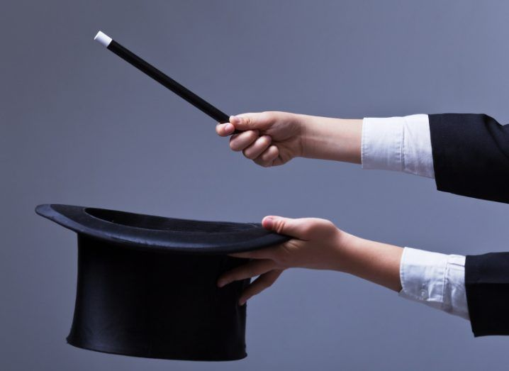 Magician hands holding black top hat and magic wand against grey background.