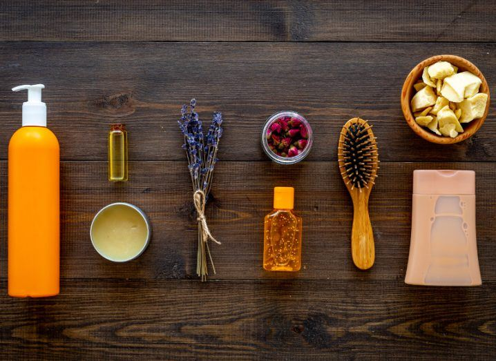 collection of hair products, including brush and spray bottle, alongside lavender and other natural products on brown wooden surface.
