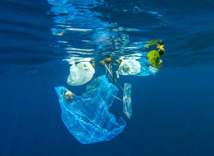 empty plastic bag and other debris floating near the surface of a bright blue ocean, symbolising the scourge of single-use plastics.
