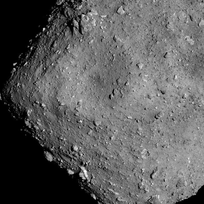 close-up of rocky surface of grey asteroid.