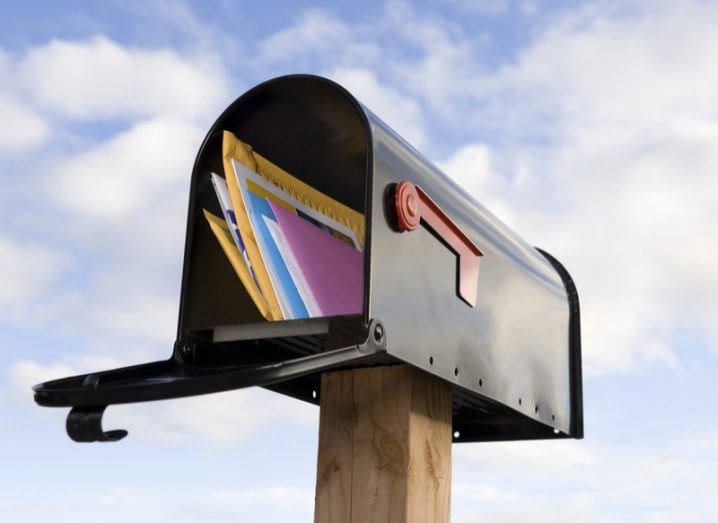 black mailbox filled with colourful letters and packages against blue sky background.