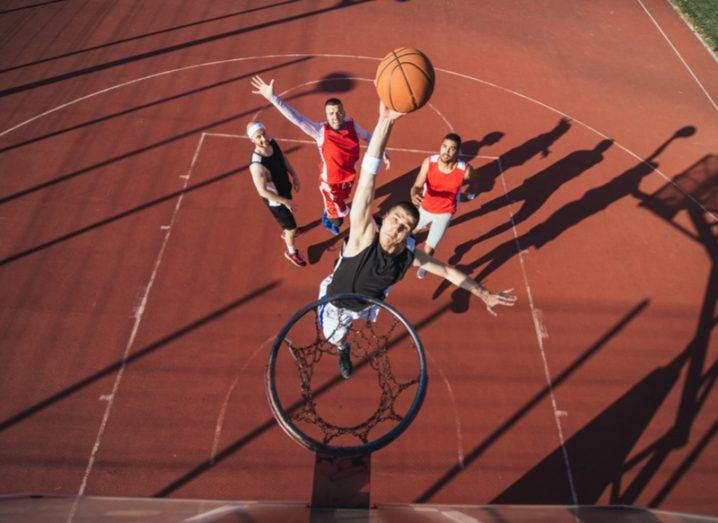 guy jumping to reach basketball hoop