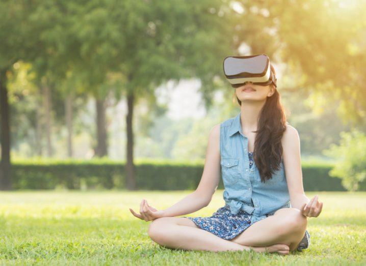 woman meditating in garden with vr headset