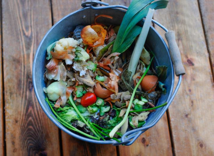 food waste, including eggshells, spring onion and cauliflower, in silver metal pail on wooden table.