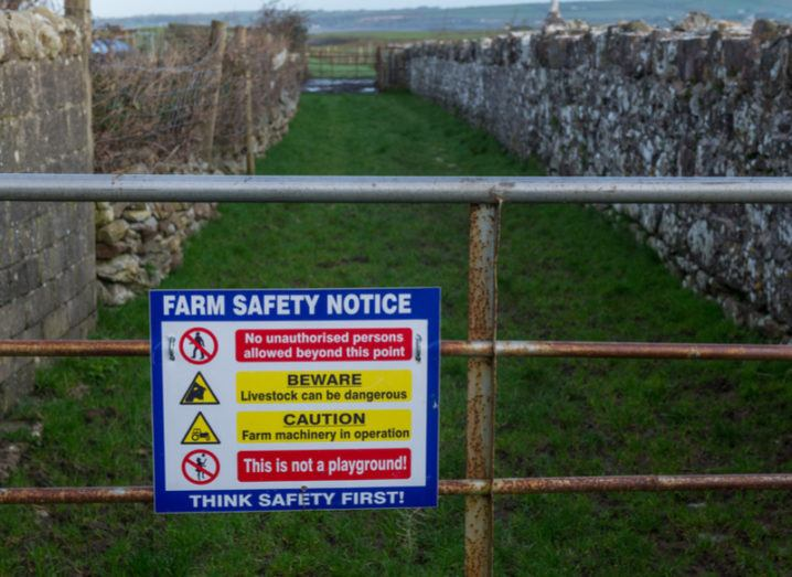 farm safety notice on rusted metal gate in front of stone walls and the grass is green.