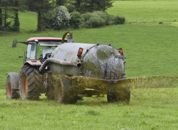 tractor spreading slurry in green field.