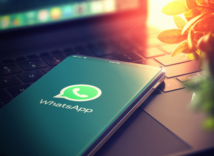 Close-up of WhatsApp logo on a smartphone, which is lying on a laptop.