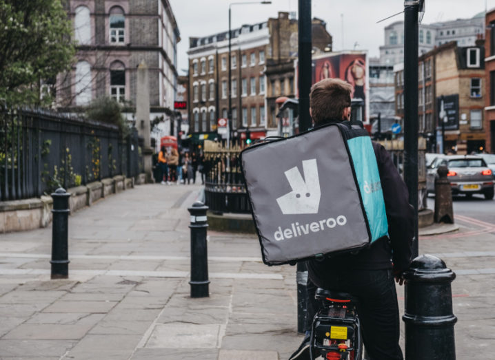 A man on a bicycle is wearing a Deliveroo bag on his back while standing on a London street path.