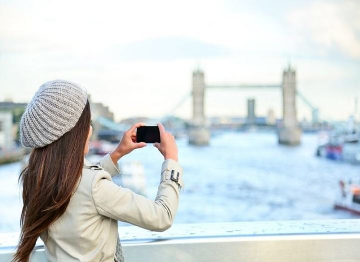 Woman taking photo of Tower Bridge