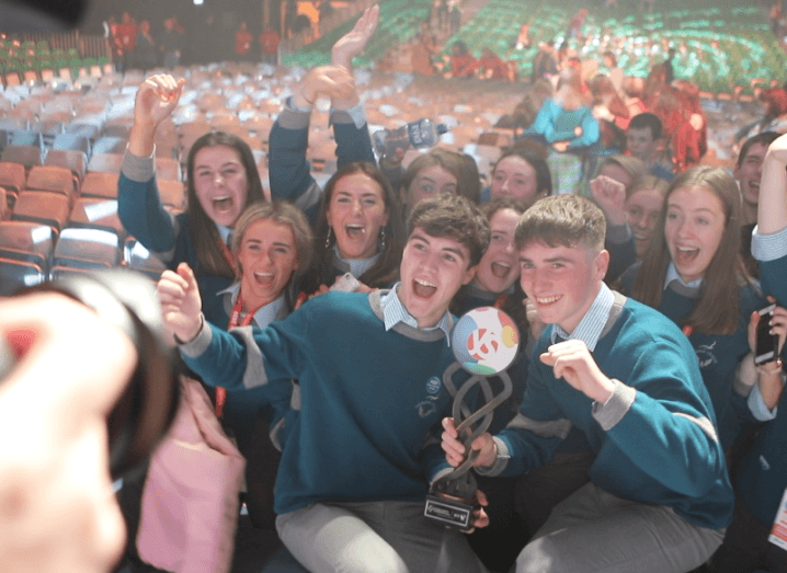 Two young men hold a trophy in front of a crowd of cheering classmates. They are all wearing green uniform jumpers with grey trousers.