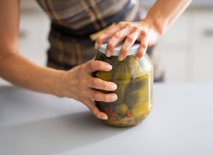 Person trying to open pickle jar