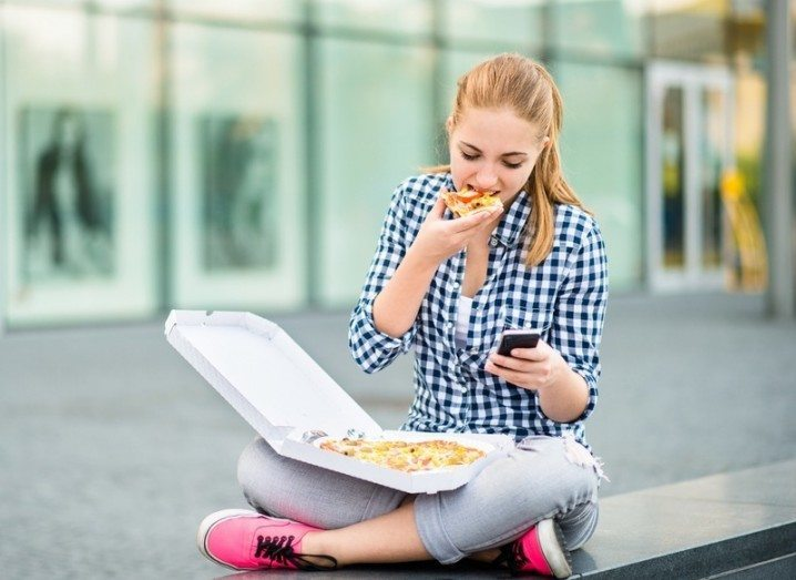 Girl eats a pizza while looking at her phone