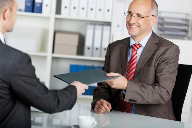Candidate handing HR Professional a CV