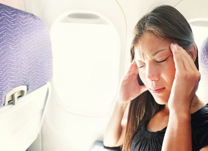 Motion sickness: woman on plane looks unwell