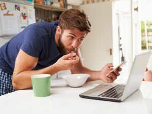 Man getting his breakfast and news at once