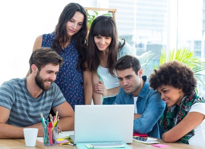PCKWCK: group gathered around laptop