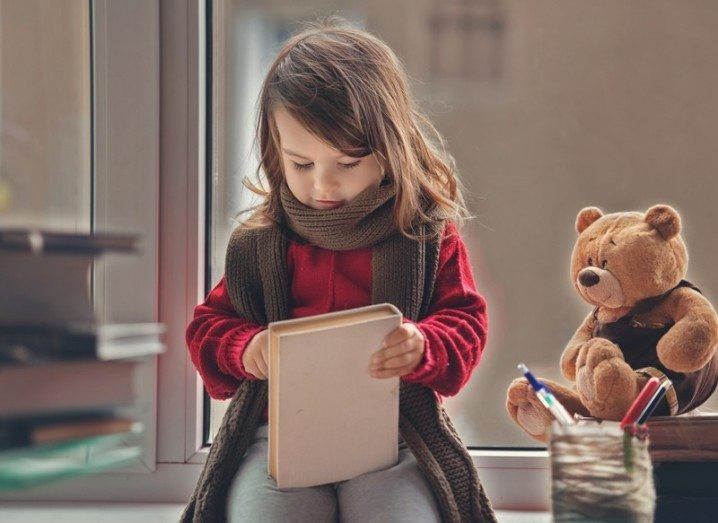 Best kids books: Child reading with teddy bear