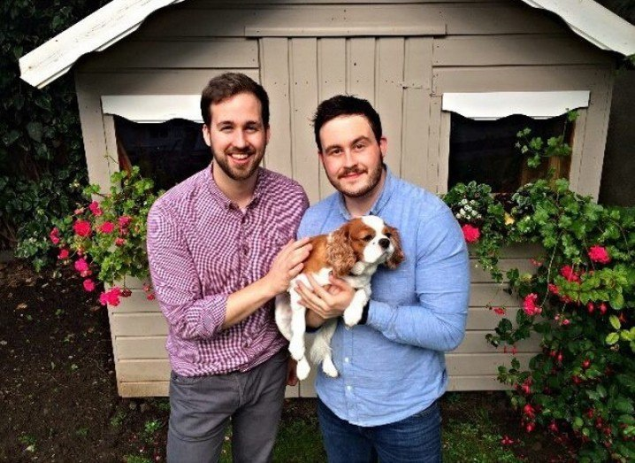 two bearded men, one in a patterned maroon shirt and the other in a pale blue shirt, holding a king charles spaniel in front of a garden shed with flowerboxes in the windows.