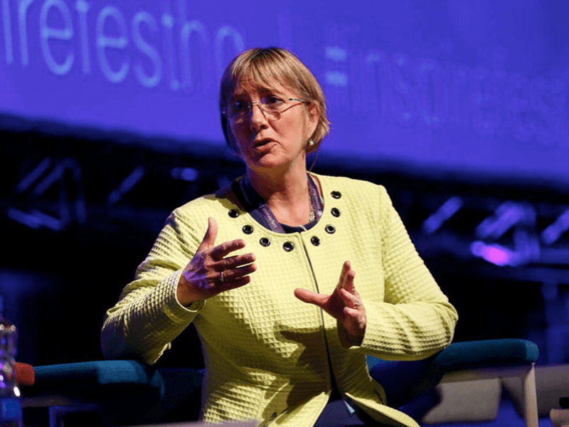 A woman gestures while speaking onstage wearing a head mic at an Inspirefest event.