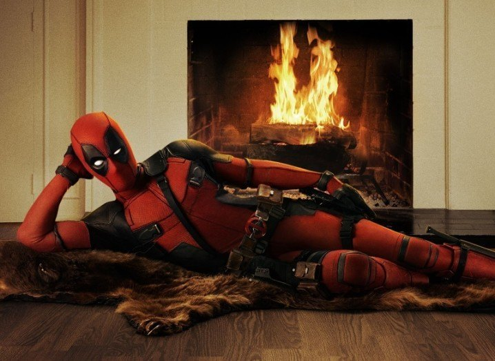 Deadpool lounges in front of fire